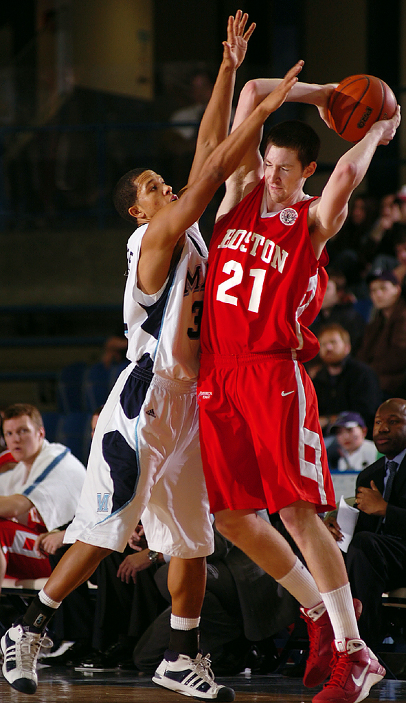 Jake O'Brien (21) of Boston University plays keep away from Maine guard Gerald McLemore in the second half of Sunday afternoon's game at Alfond Arena in Orono. B.U. won the game 73-62.