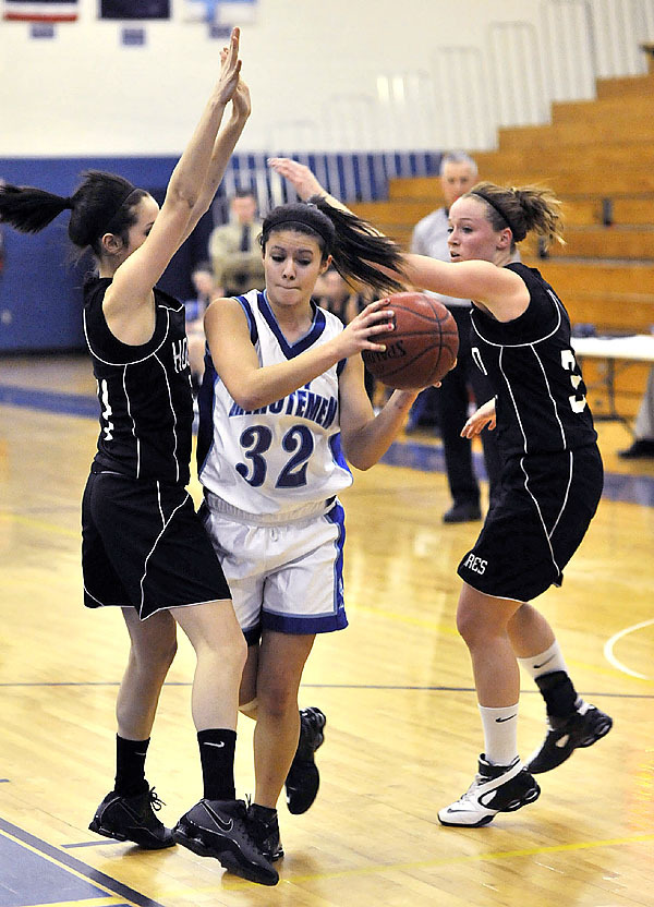 Stearn's Katie Mills, (32), tries to drive between Houlton's Vanessa Sanderson, (24), and Lainey Herring, (33), in the second half of their game in Millinocket on Friday. Buy Photo