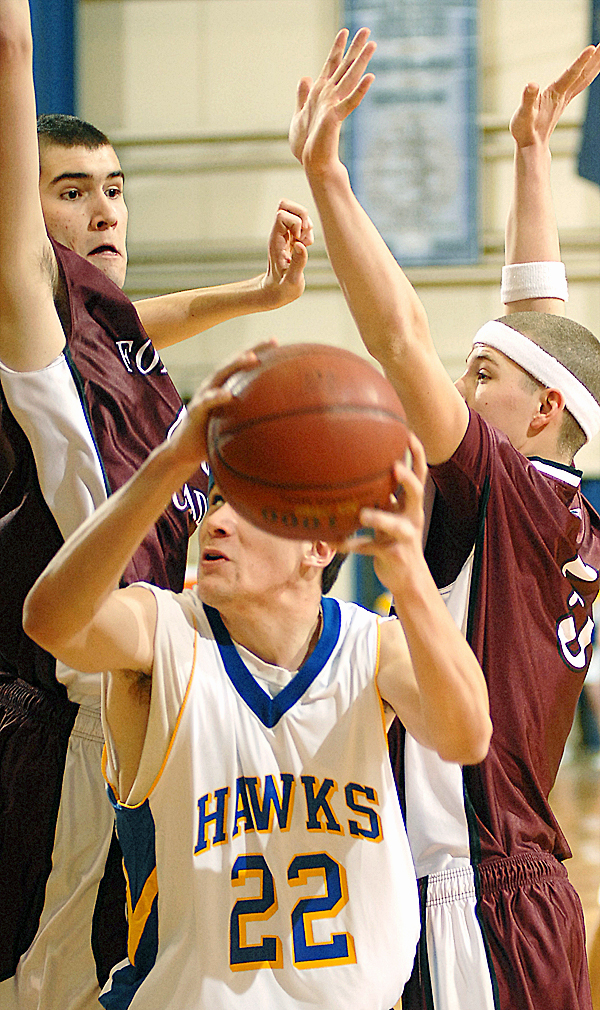 Hermon's Aaron Jellison is fouled by Foxcroft defender Chase Hutchinson (23, second from right) as he and teammate James Johnson (40) try to block the shot in the first-half of the boys Saturday Class B quarterfinal game.  Buy Photo
