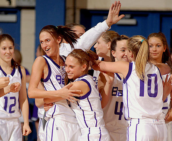 Bapst's Samantha Maquillan (left) and Morgan Chasse celebrate with their team after winning the girls Class B semifinal game against Presque Isle 37-26 on Wednesday.  Buy Photo