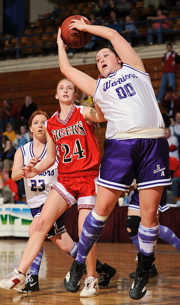 Southern Aroostook's Lauren McGary, right, snags a rebound under the watchful eye of Fort Fairfield defender, Courtney Churchill, center, and fellow Warrior Janel Rockwell, left , on Thursday, Feb. 19, 2009 at the Bangor Auditorium during 2nd period action. Buy Photo