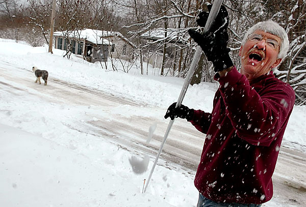 Mike Morcom of Orono rakes snow from the roof of his Broadway home in the early afternoon of Monday, February 23, 2009, as his dog Argus plays in the background.  Morcom, a teacher,  spent last week vacationing in California.  &quotThere was no snow in San Jose,&quot he chuckled.   Buy Photo