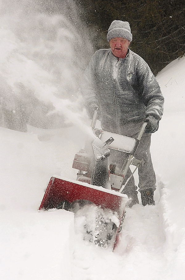 Herbert Pettengill clears his Buck Street walkway after a snowfall blanketed Bangor on Monday.