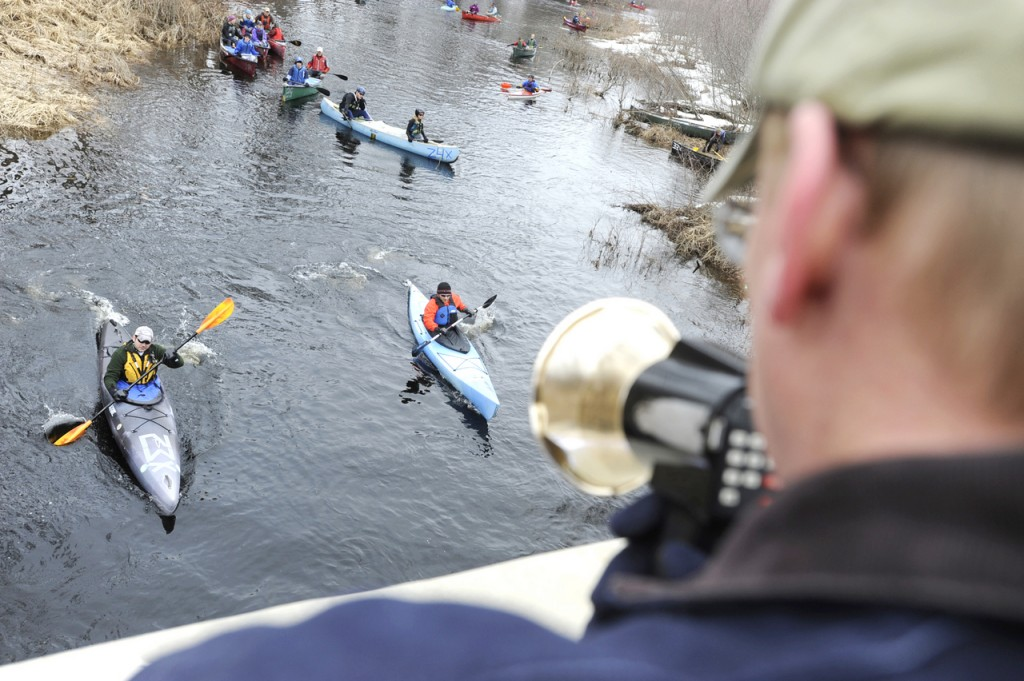 Race volunteer Jeff Rauch (foreground) of Belfast gets on the megaphone to stagger start two kayakers in the St. George River Race in Searsmont on Saturday morning. There were 107 boats in the water for the six-mile race that marks the start of the local paddle race season.  Buy Photo