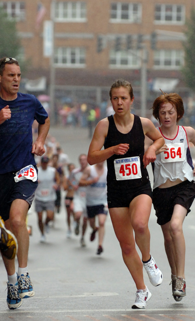 Brenna Walsh (450) runs up State Street during the Fourth of July 3K in Bangor on Saturday morning, July 4, 2009. Walsh finished first in the women's race with a time of 10:18.  Buy Photo