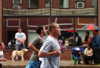 Runners run down Exchange Street during the Fourth of July 3K in Bangor as spectators watch in a light rain Saturday morning, July 4, 2009.  Buy Photo