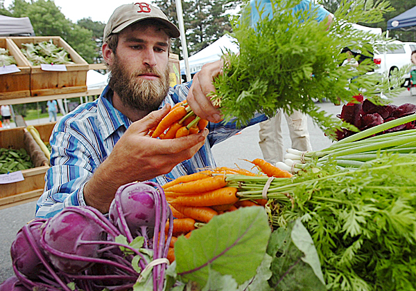 Gene Ripley of Ripley Farm in Troy replenishes his stand with fresh carrots at the Orono Farmers' Market on Tuesday, July 21, 2009.  Located off of College Avenue, during the summer and early fall the market operates from 2pm to 5:30 on Tuesdays, and 8am to 1pm on Saturdays.  (Bangor Daily News/Kate Collins)