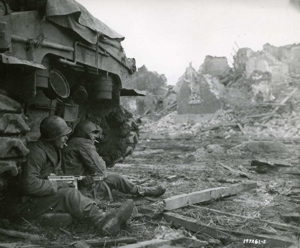 With German shells screaming overhead, American soldiers from the 9th Infantry Division seek shelter behind a tank.  The town of Geich, Germany, is in ruins in the background, and it was still under heavy shelling Dec. 11, 1944.