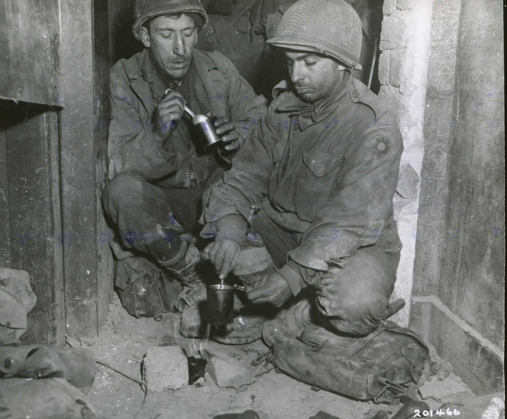 Pfc. Edward E. Gladsford (left) of Chicago, Ill., and Pfc. Oscar L. Lombardi of Los Angeles, Cal., soldiers from the 9th Infantry Division, eat canned  &quotC&quot rations in a doorway in Germany on Feb. 27, 1945.  The rations were heated over a small fire.