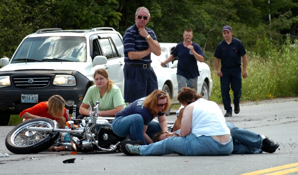 Eye witnesses to a motorcycle crash on Route 15 and Hudson Hill Road in Corinth comfort the two victims while waiting for an ambulance and first responders Tuesday, July 28, 2009. The man and woman on the motorcycle were taken to Eastern Maine Medical Center for treatment of &quotvery serious, possibly life-threatening injuries,&quot according to Penobscot County Sheriff's Office Chief Deputy Troy Morton. (Bangor Daily News/Bridget Brown)