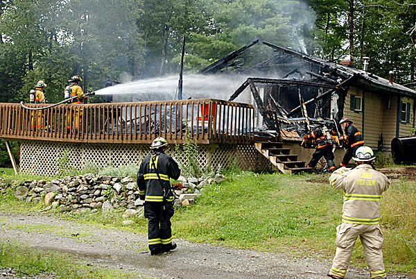 Holden, Eddington and Brewer Firefighters  extinguish flames on a home located at 485 Levenseller Road in Holden on Thursday, July 30, 2009.  No one was at home at the single story wooden structure shortly after noon at the time the fire started, a passer-by spotted the flames and searched the home as his wife dialed the fire department.