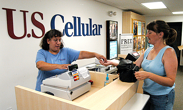 Nancy Guiod [left] hands change to a customer at the Katahdin Cellular store on West Broadway in Lincoln on Friday. The store will get a total renovation as part of U.S. Cellular?s response to increasing competition from other cellular telephone providers to northern Maine, Guiod said. (Bangor Daily News/Nick Sambides Jr.)
