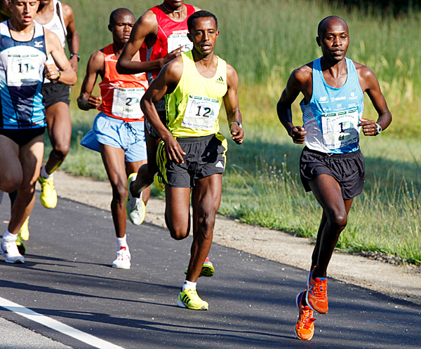 Ed Muge, (1), center, of Kenya, and Tekeste Kebede, (12), left, of Ethiopia, lead the pack Saturday, Aug. 1, 2009 during the Beach To Beacon 10-kilometer road race in Cape Elizabeth, Maine. Muge went on the win the race. (AP Photo/Joel Page)