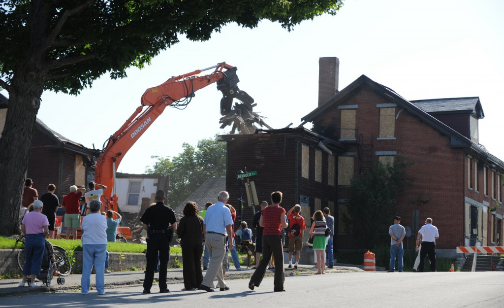 A crowd gathers  at the intersection of Bennoch Road and Forest Ave. in Orono on Tuesday, August 4, 2009 to watch the demolition of the historic Katahdin Building located at 6 Bennoch Road. Fire damage from a June 9, 2009 fire  damaged the building beyond repair. (Bangor Daily News/Kevin Bennett)