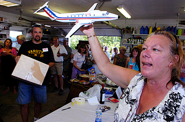 Hostess Adrienne Buzzell holds up a small scale model of a Bat Harbor Airlines Beechcraft 1900 during a raffle at the airline reunion party at her and her husband Bruce Buzzell's home in Hermon Saturday, August 15, 2009. Over 75 former employees (and family members) of the now-defunct Bar Harbor Airlines and its local successors at BIA-- Eastern Airlines and Continental Airlines --turned out for the party from as far away as Florida and Hawaii. Holding the raffle box (on left) is fellow party organizer Fred Gaspar of Holden. &quot It's like an extended family, being in the airline business, &quot said fellow partygoer and former employee Cheri Neptune (not pictured) of Poland Springs. &quotWe still all call each other after all these years.&quot (Bangor Daily News/John Clarke Russ)