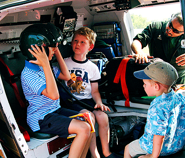 Nine-year-old Gabriel Manzo of Millinocket tries on a LifeFlight helicopter helmet while his friends, 7-year-old Michael Clark and 2?-year-old Robert Cyr, also of Millinocket, look on Monday. (Bangor Daily News/Nick Sambides Jr.)