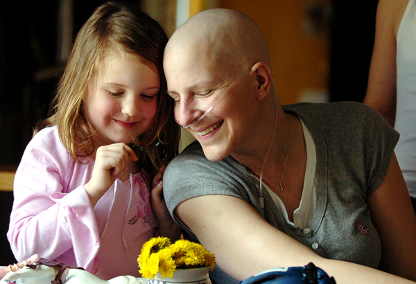 Sonya Barclay (right) and her daughter, Madyson (left) share a tender moment on Thursday in the kitchen of their Old Town home after Madyson brought dandelions from the yard for her mother who is battling cancer. The Barclay family learned Friday that they will be getting a new home courtesy of several Old Town businesses.  (BANGOR DAILY NEWS PHOTO BY KEVIN BENNETT)