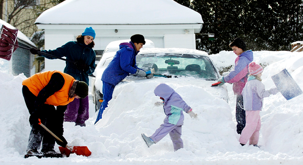 Bruce Freedberg (from left0, Rosa Tiemann, Donna Tiemann, Maayan Freedberg, Elsa Tiemann and Chana Bayla Freedberg all pitch in to clear snow from the Tiemanns' car on Congress Street in Bangor on Monday. The Tiemanns were attending a Hanukkah party at the Feedbergs' when Sunday's snowstorm forced them to spend the night before venturing back to Ellsworth on Monday.  (BANGOR DAILY NEWS PHOTO BY KEVIN BENNETT)
