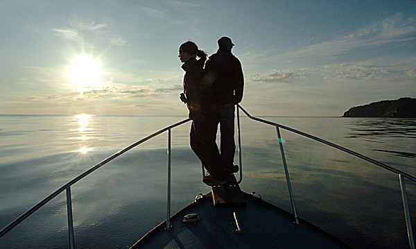 New England Aquarium researchers Jessica Taylor (left) and Jon Cunha watch for North Atlantic right whales and other marine life as they conduct a survey in the Bay of Fundy near Grand Manan (right) on Thursday, Aug. 20, 2009 at dawn. Once hunted to the brink of extinction, the critically endangered right whale migrates each summer up the Atlantic seaboard from their birthing area near the Florida or Georgia coast, to the Bay of Fundy where they feed and socialize. Scientists from the aquarium have summered in Lubec for the past 30 years to conduct their research on the species which is thought to include less than 400 whales. (Bangor Daily News/Bridget Brown)