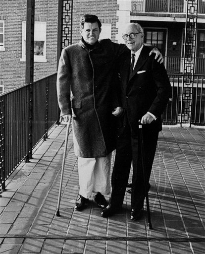 FILE -- Sen. Edward M. Kennedy, left, takes a stroll with his father former ambassador Joseph P. Kennedy on an open porch at New England Baptist Hospital in Boston, Dec. 8, 1964, where the senator is recuperating from the broken back he suffered in a plane crash.  Sen. Ted Kennedy has died after battling a brain tumor his family announced early Wednesday Aug. 26, 2009.  (AP Photo)