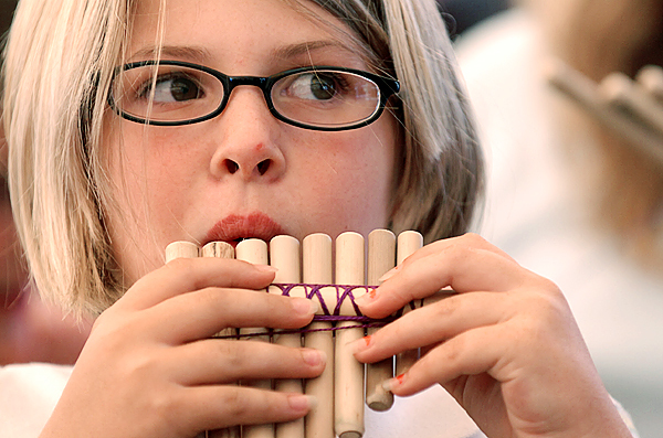 Caitlyn Conley, 10, of Glenburn tries playing the panpipe she made with the help of the members of Andes Manta, an Andean music group made up of four brothers, in the family area Sunday at the 2009 American Folk Festival on the Bangor Waterfront.  Buy Photo