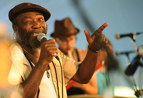 Legendary reggae singer-songwriter Clinton Fearon winks at his percussionist Ire on Sunday at the 2009 American Folk Festival Dance Stage as the eight-member band had all feet on the dance floor moving for their last song of the festival. Buy Photo