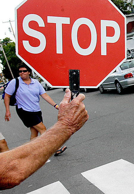 BRAKE FOR ROAD SCHOLARS   Edward Tracy's hand holds aloft a sign to motorists as the crossing guard ensures the safety of youngsters and parents navigating the roadway at Forest Avenue and Somerset Street in Bangor after the first day of classes Thursday at Abraham Lincoln School. (PHOTO BY ERIN FREDRICHS )