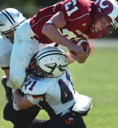 Skowhegan's Devin Withee (41) and Kaleb Austin (upper left) tackle Bangor's Lonnie Hackett (21) in the second quarter of Saturday's game, Sept. 5, 2009 at Cameron Stadium in Bangor. The game fell on the 50th anniversary of an NFL exhibition game between the Giants and the Packers, the only such game to take place in Maine. Buy Photo