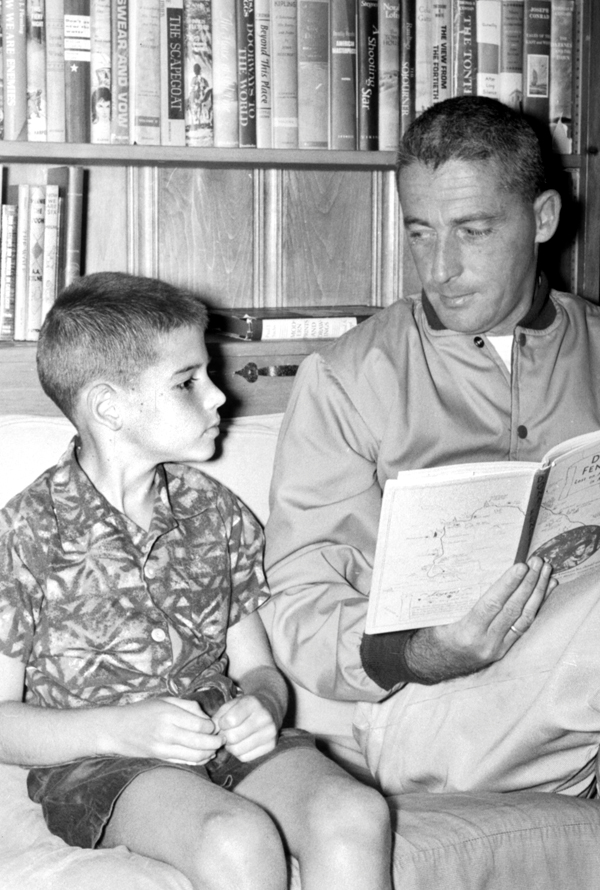 Captain Donn Fendler shows &quotLost on a Mountain in Maine&quot to his son, Dennis , 8, during a visit to Palmyra in July 1962.  BANGOR DAILY NEWS PHOTO BY DON BROUGH