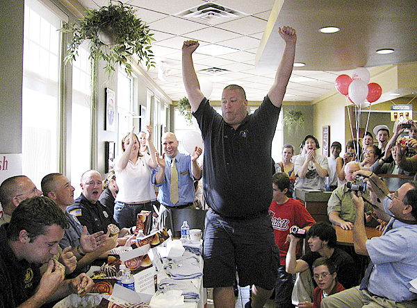 Justin Hills of Camden First Aid struts his stuff Thursday at the Rockland Tim Horton's after he won the law enforcement doughnut-eating challenge. The event is a fundraiser for Special Olympics of Maine. Buy Photo