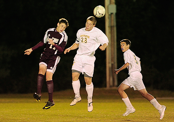 Mike Curtis (left) of Ellsworth and Colton Gross (23) of Hermon go up for a head ball during Thursday night's Class B soccer match at Hermon on Thursday night, as Hermon's Tyler Kelley (3) trails the play. Buy Photo