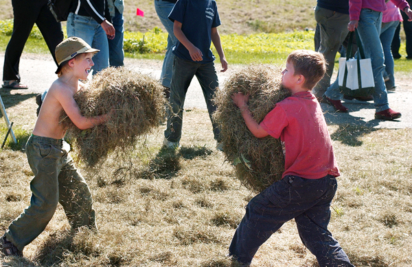 Guthrie Purinton-Brown, 8, (left) of Monroe and his friend Jackson Donnelly, 7, of Searsport have an impromptu hay fight on Friday, Sept. 19, 2008 at the Common Ground Fair in Unity.    BANGOR DAILY NEWS PHOTO BY BRIDGET BROWN  (WEB EDITION PHOTO)
