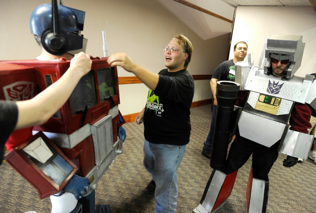Henry Dow (center) helps make sure Optimus Prime (a Transformer character played by Ray Maddocks  of Morrill) looks his best at the BangPop Comic Book and Pop Culture Convention on Saturday at the Bangor Civic Center. Behind them are Rich Nielsen of Searsport and Elmer Nickerson (far right) of Searsport, who is costumed as Megatron, another Transformer character, replete with a fusion cannon. Buy Photo