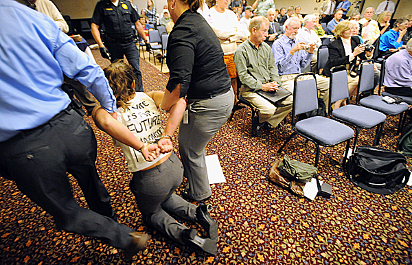 One of the protesters is taken out of the room during a meeting of the Land Use Regulatory Commission at Ramada Inn in Bangor Wednesday afternoon, Sept. 23, 2009.   The commission voted to allow Plum Creek Timber Co. to develop parts of the Moosehead Lake region. (Bangor Daily News/Gabor Degre)