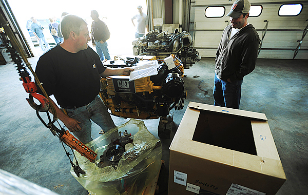 Billings Diesel and Marine mechanic Troy Morey, left, unpacks the marine gear from a crate as lobster fisherman Jason Witham, right, watches at the company's Stonington facility on Thursday, September 24, 2009. Witham's boat, Siren, is having the older 2-cycle engine replaced with a new 4-cycle, Cat C-9 diesel engine as part of the Maine Department of Enviromental Protection's, Repower Program. Witham's old engine can be seen on the floor in the background. (Bangor Daily News/Kevin Bennett)