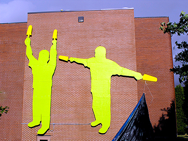 A tarp is dropped from the top of Pullen Hall at the University of Maine at Presque Isle on Friday to unveil the IT Men - two giant, 20-foot-tall, lime green traffic control figures constructed out of plywood that once stood at the concert gates of the IT music festival put on by Phish in August, 2003.  The IT Men have been installed on the west end of Pullen Hall in honor of the Phish Retrospective, being hosted by UMPI's Reed Art Gallery from Sept. 28 to Nov. 21. (BANGOR DAILY NEWS PHOTO BY JEN LYNDS)