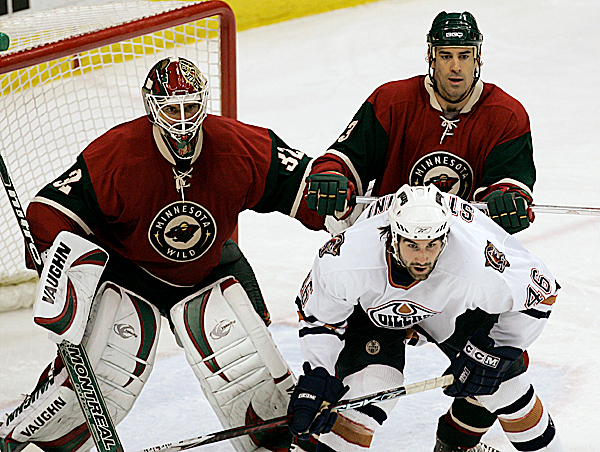 Minnesota Wild defenseman Keith Carney (top right), a former University of Maine player, tries to clear Edmonton Oilers right wing Zack Stortinin from in front of the net during a game last week. Carney's Wild will face Dustin Penner, another former Black Bear, and the Anaheim Ducks in the first round of the playoffs. (AP Photo/Ann Heisenfelt)