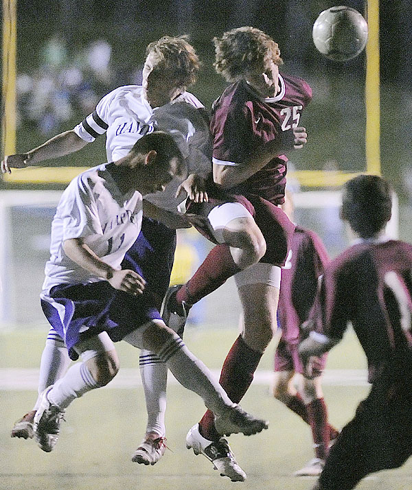 Bangor's Clark Noonan, (25), tries to get a header on goal as Hampden defenders Austin Michaud, (9), and Jeremiah Leong, (11), try to clear the ball in the second half of their game in Hampden, Thursday, Sept. 24, 2009. Bangor Daily News/Michael C. York