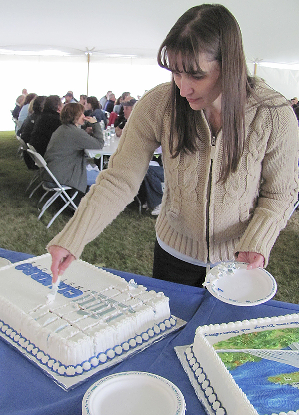 Donna Jacques of Skowhegan, an executive administrative assistant for Cianbro Corp. in Pittsfield, cuts a cake that was shared by hundreds of Cianbro employees Friday during a celebration of 60 years in business. (Bangor Daily News/Christopher Cousins)
