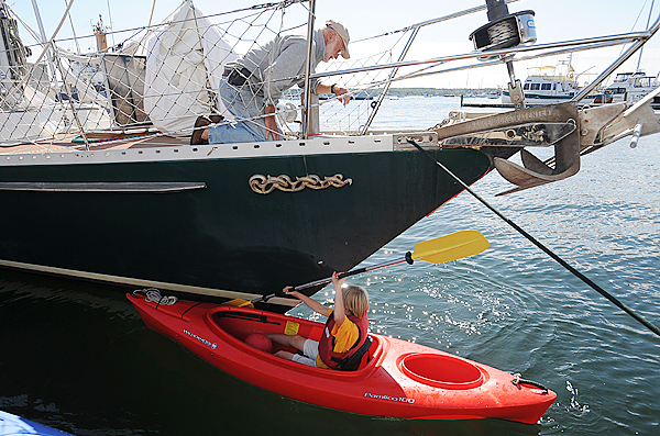 David Lyman (top) works on a hatch cover as his son Havanna returns from a little kayaking around their sailboat the Searcher in Rockland Harbor last week.  They were making last minute repairs in preparation for a long sailing voyage aboard the 57 foot boat that could take them around the world.  &quotWe planned out the first six months or so and then we will see how things are going.  We will possibly return to Maine after that and see where we go next.&quot   (Bangor Daily news/Gabor Degre)