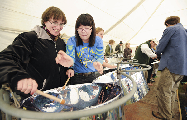 &quotThis is great, I always wanted to play steel drums.&quot said Leona Hosack, left, of South Berwick after getting a steel drum playing lesson on Friday, September 25, 2009 from George Stevens Academy Student, Minyoung Jung, at the Common Ground Fair in Unity. Nigel Chase, left, offered those in the audience a chance to learn from the students and them lead them on a short song.  (Bangor Daily News/Kevin Bennett)