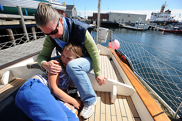 Julie Lyman comforts her daughter Renaissance after something fell into her eye while playing aboard their 57 foot sailboat the Searcher.  They were making the final preparations for a long jurney that may take the family of four around the world. (Bangor Daily News/gabor Degre)