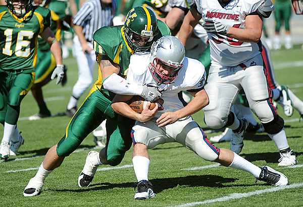 Husson University's Bobby Gilbert (left) tackles Maritime College's quarterback Anthony Gagliano during the second half of the game in Bangor Saturday afternoon. (Bangor Daily News/Gabor Degre)
