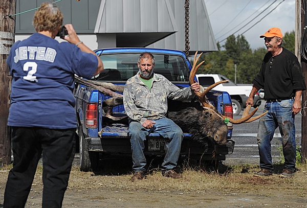 Martha Dickinson, left, of Oakfield, photographs her husband, Robert Dickinson, center, and Carl Croy, right, at the tagging station at M.A.C.S. Trading Post in Houlton after Robert dropped a 752 pound bull moose on Monday, September 28, 2009. (Bangor Daily News/Kevin Bennett)