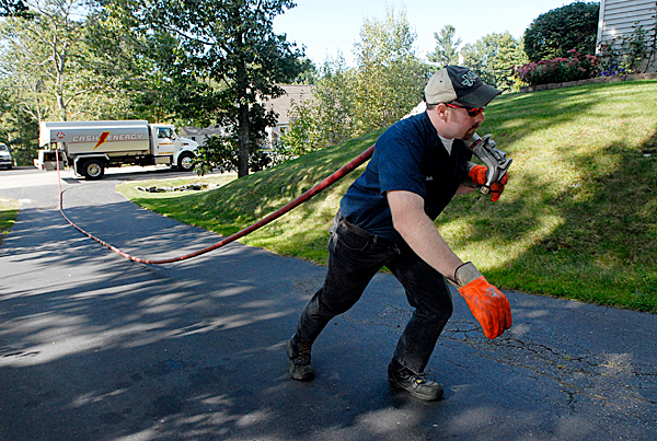 Kieth Franklin a delivery driver for Cash Energy drags the oil hose up a driveway in Old Orchard Beach, Maine for a delivery on Friday, Sept. 25, 2009.  (AP Photo/Shawn Patrick Ouellette)