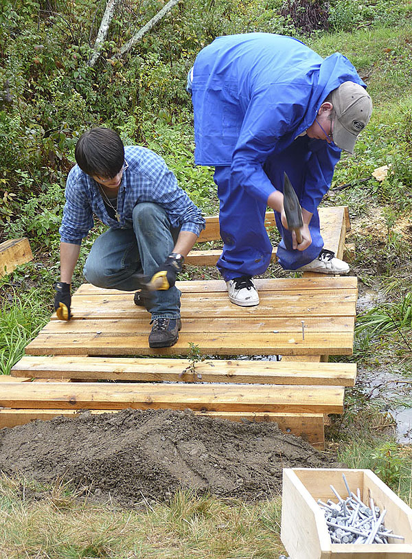Shayne Cummings of Marion, left, and Zach Hatch of Trescott help build a small bridge Tuesday at Cobscook Bay Learning Center in Trescott. The boys were part of a group of Washington Academy students who participated in Stewardship Day at the center, which is celebrating its 10th anniversary this week with daily events, gatherings and celebrations. (Bangor Daily News photo by Sharon Kiley Mack)
