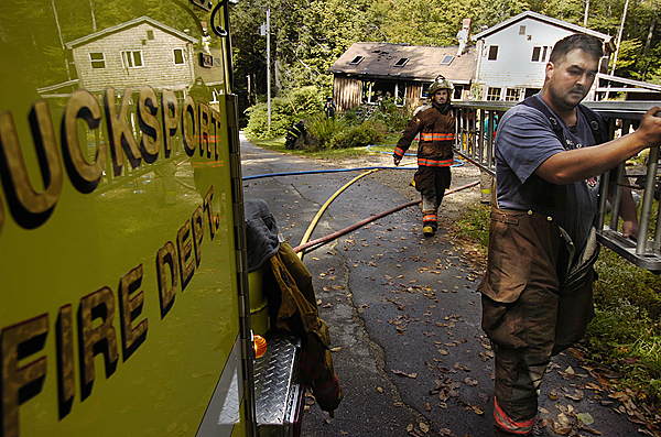 Orland firefighters Casey Soper (front) and Dustin Wentworth walk a ladder back to their department's truck after joining Bucksport, Penobscot and Orrington fire departments to fight a house fire on Verona Park Road on Verona Tuesday morning, September 29, 2009. Bucksport Fire Chief Pam Payson said their company responded to the call at 9:42 a.m. and knocked down the fire within 15 minutes of arrival. The home sustained considerable fire damage. (Bangor Daily News/John Clarke Russ)
