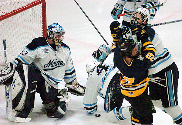(BANGOR DAILY NEWS PHOTO BY JOHN CLARKE RUSS)  CAPTION  University of Maine goaltender Dave Wilson protects as teammate  Mike Banwell falls on the puck and teammate Simon Denis-Pepin (far right)  scuffles with Merrimacks Ryna Flanagan at the begining of the first period of play at Alfond Arena in Orono Friday night. (Bangor Daily News/John Clarke Russ)