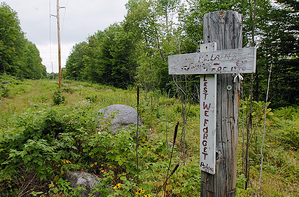 A makeshift cross hangs Saturday on the stump of a utility pole along a power-line clearing behind Schenck High School in East Millinocket where Joyce McLain's body was found Aug. 10, 1980. Joyce's name and dates have long since faded, but the words &quotLest we forget&quotare still visible.  (BANGOR DAILY NEWS PHOTO BY KEVIN BENNETT)  CAPTION  A make shift cross hangs Saturday, August 30, 2008 on the stump of a utility pole along a powerline clearing behind Schenck High School  in East Millinocket were Joyce Mclain's body was found on August 10, 1980. Joyce's name and dates have long since faded, yet the words, &quot Lest we forget&quot are still visable.(Bangor Daily News/Kevin Bennett)