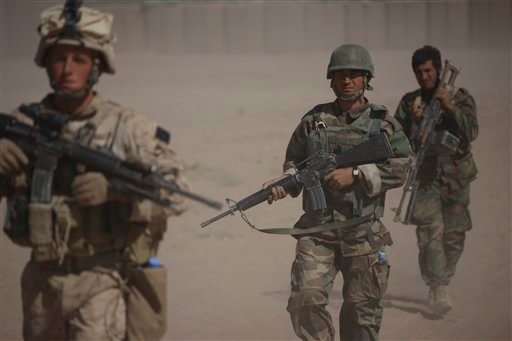 A U.S. Marine, left, with Bravo Company, 1st Battalion 5th Marines walks in a joint patrol with Afghan National Army soldiers, in Nawa district, Helmand province, southern Afghanistan, Saturday, Oct. 3, 2009. (AP Photo/Brennan Linsley)